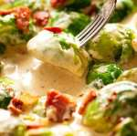 Fork picking up sautéed Brussels sprouts in a creamy sauce