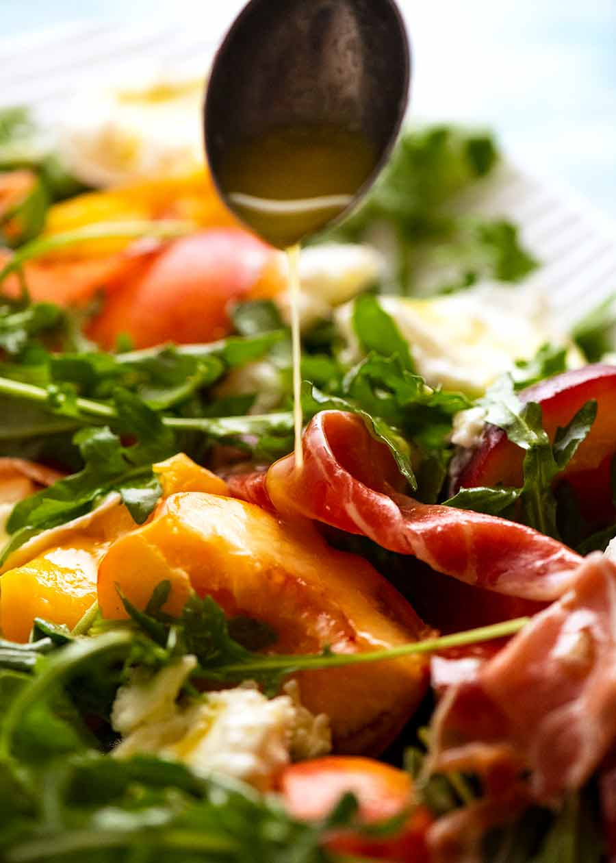 Drizzling lemon dressing over peach salad