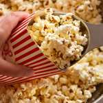 Scooping Slightly sweet and salty butter popcorn into popcorn holder