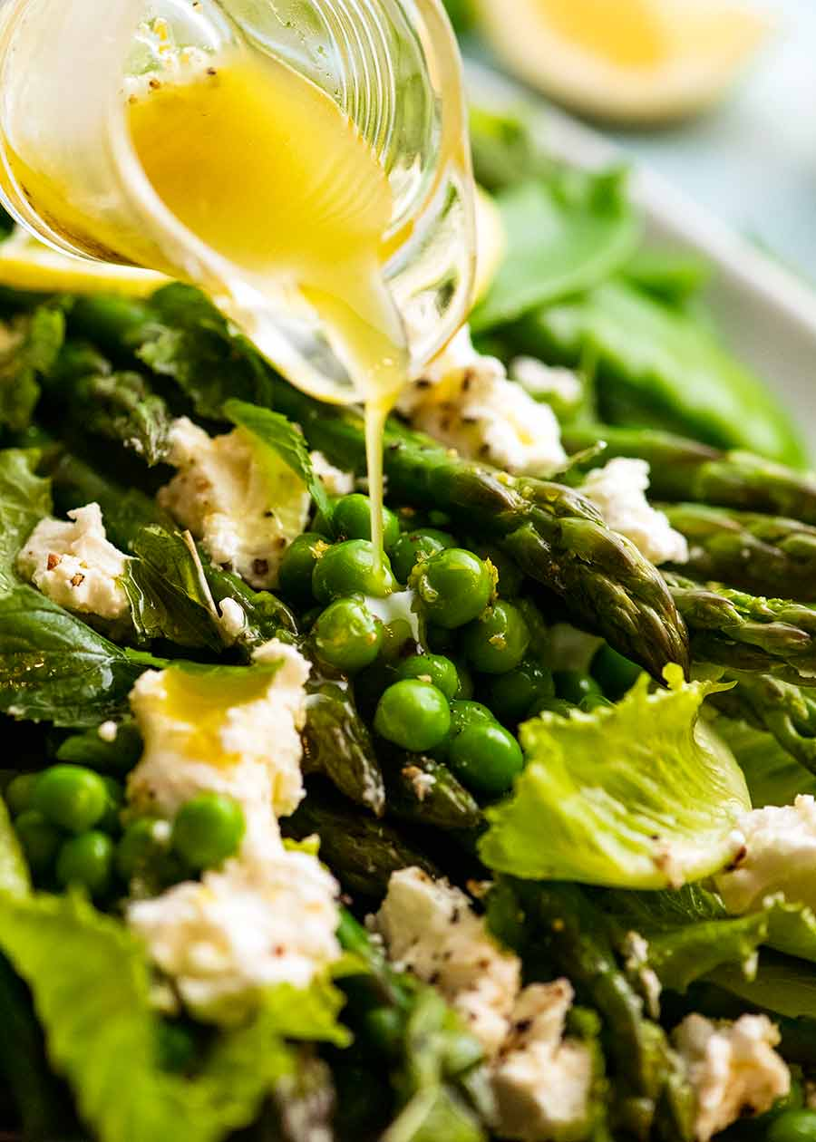 Drizzling lemon dressing over Spring Salad - with asparagus, peas, snow peas, baby cos lettuce (romaine) and goats cheese