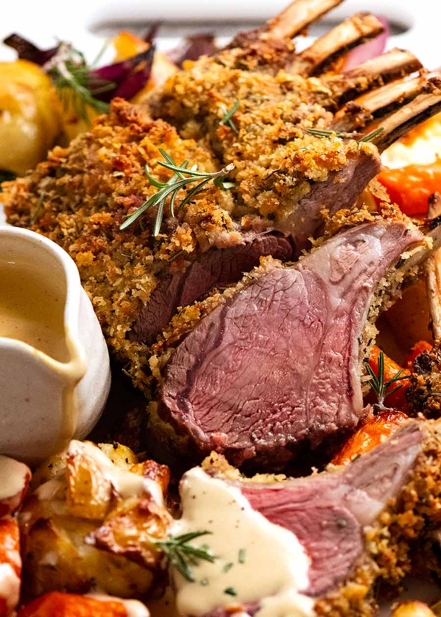 Rosemary Crumbed Rack of Lamb on a platter with roasted vegetables
