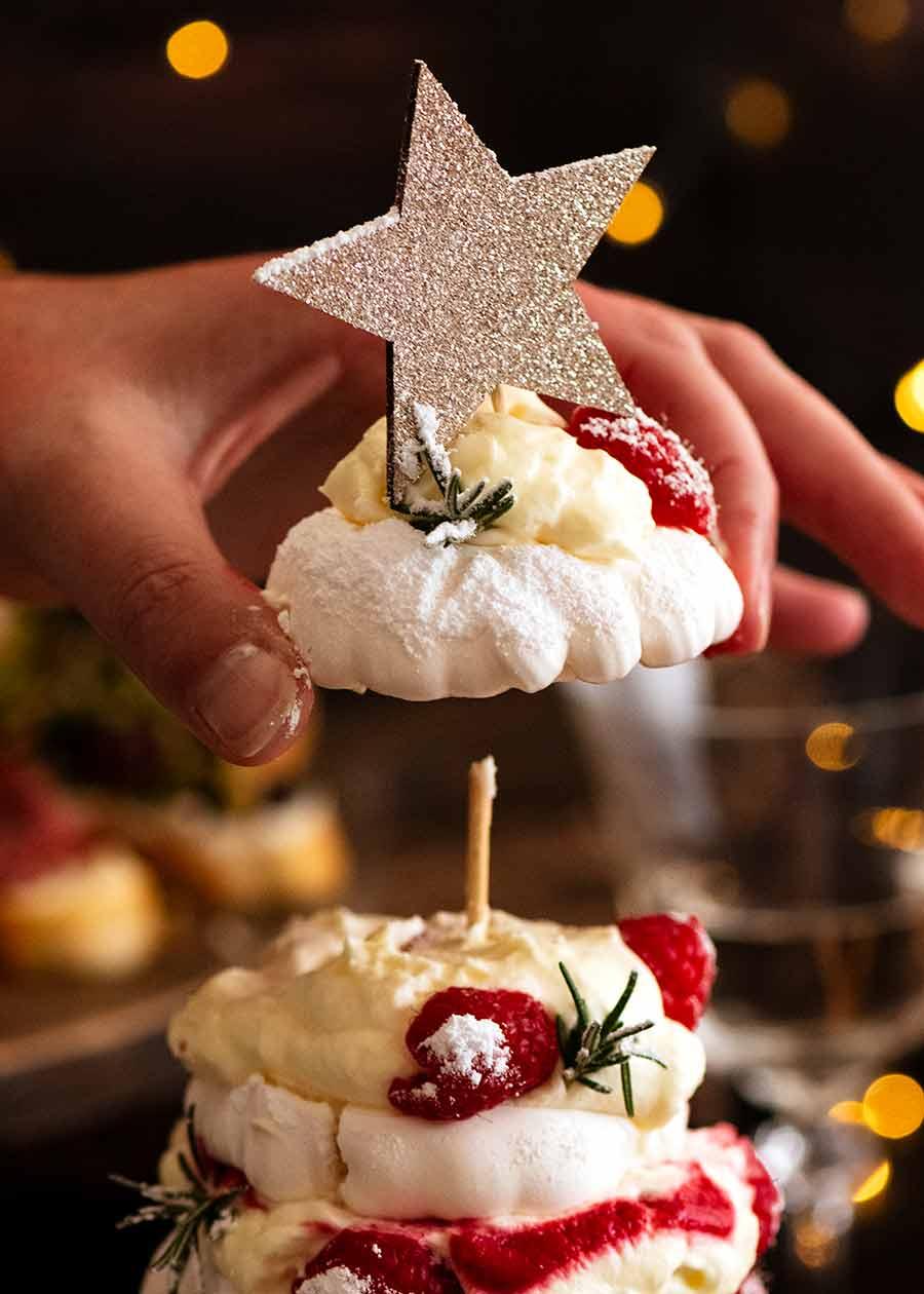 Handing picking up top layer of Pavlova Christmas Tree Dessert
