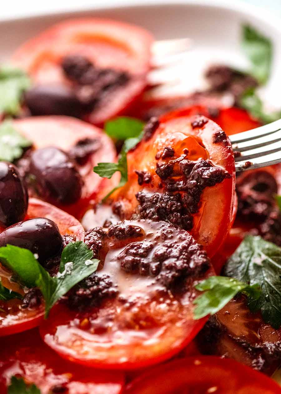 Fork picking up piece of Tomato Salad with Olive Tapenade