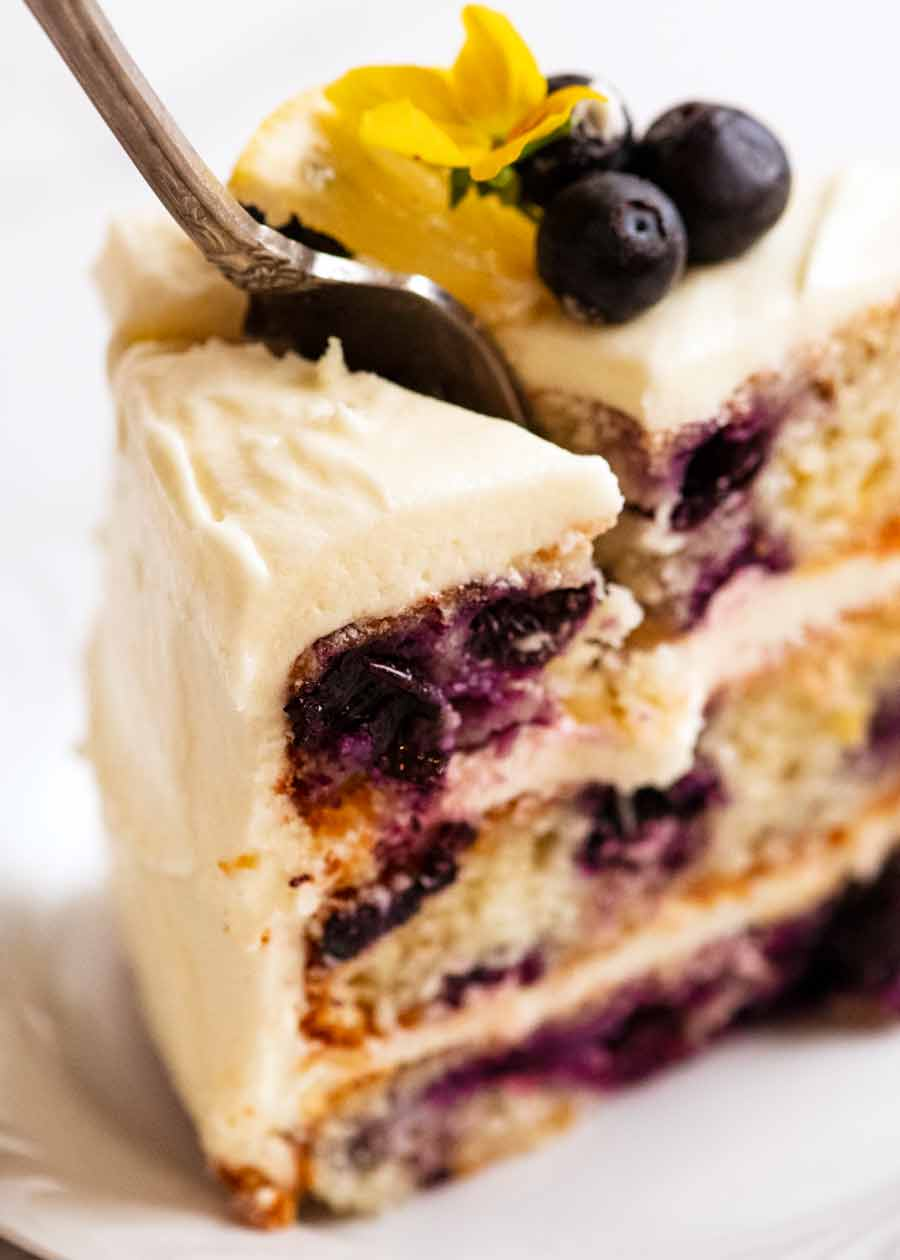 Fork cutting into Blueberry Cake with Lemon Cream Cheese Frosting