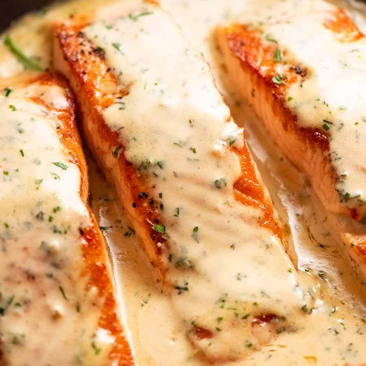 Close up of Creamy Herb & Garlic Salmon Sauce in a skillet, fresh off the stove