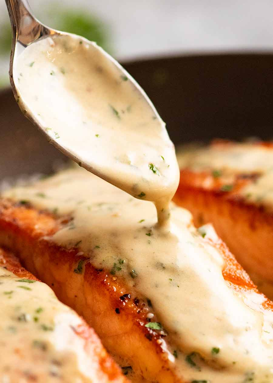 Drizzling cream Herb & Garlic Salmon Sauce over pan seared salmon