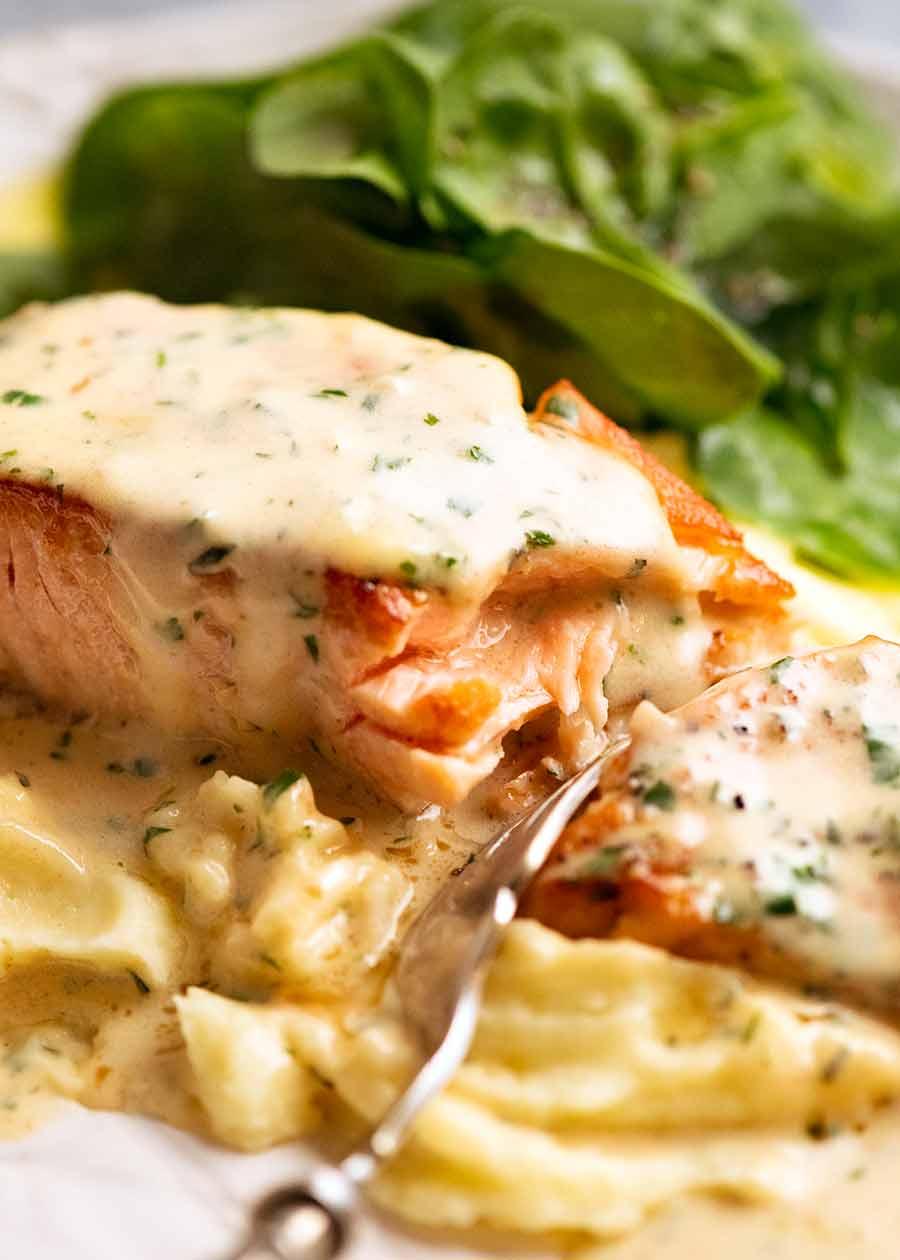 Fork cutting into Creamy Herb & Garlic Salmon Sauce