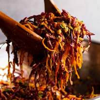 Wooden spoons tossing Cabbage and Carrot Thoran-style salad (Indian Salad)