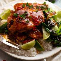 Pile of Asian Chilli Chicken served over rice with steamed asian greens on the side