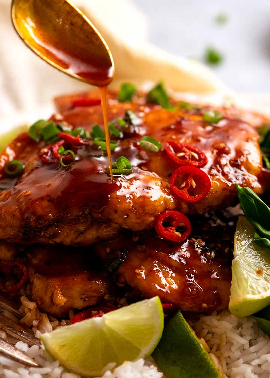 Close up of spoon drizzling sticky spicy sweet sauce over Asian Chilli Chicken