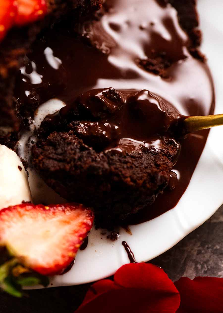 Close up of spoon scooping up Molten Chocolate Cake with chocolate lava