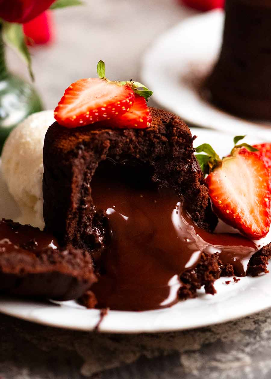 Close up of Molten Chocolate Cake with chocolate lava pouring out, decorated with strawberries and a scoop of ice cream