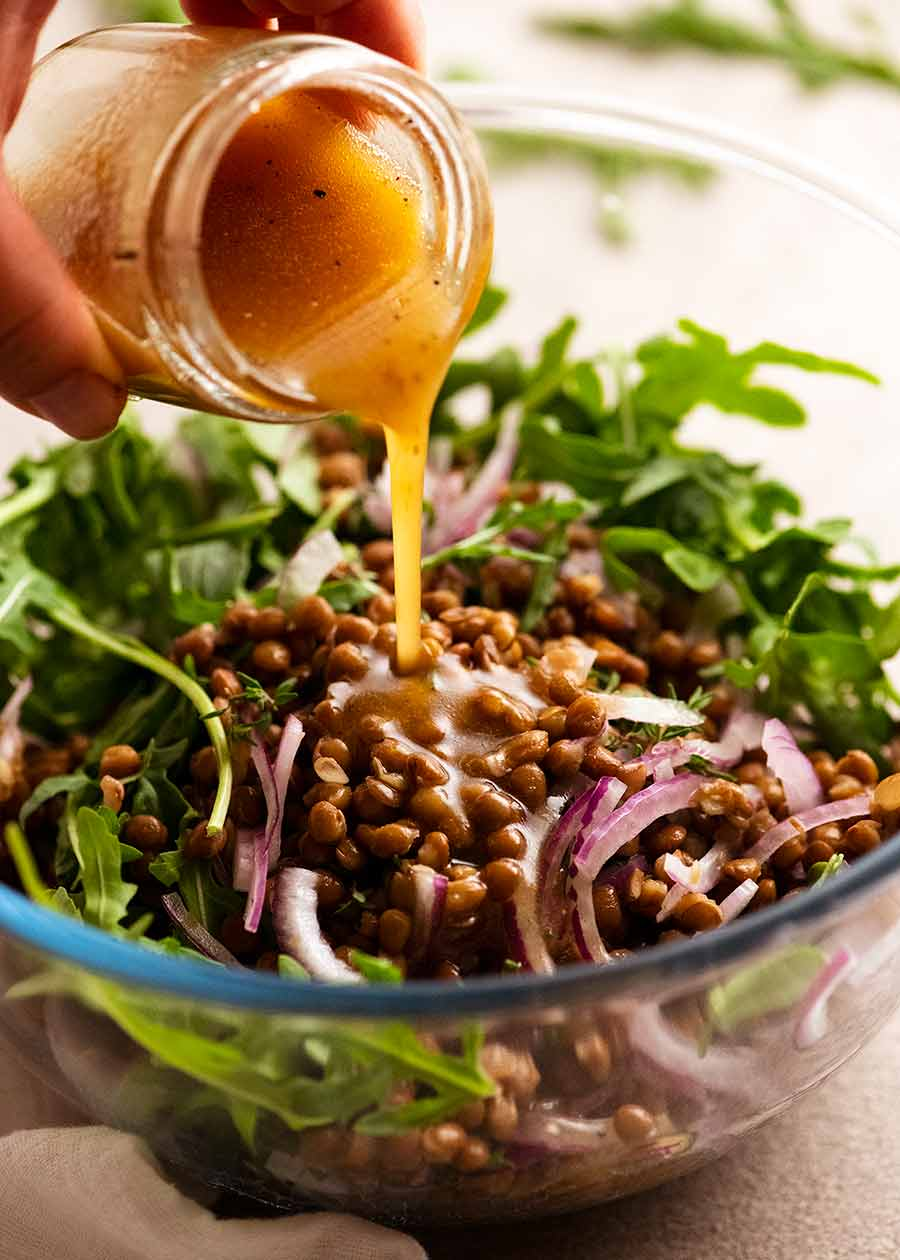 Pouring dressing over Honey Cinnamon Pumpkin Lentil Salad