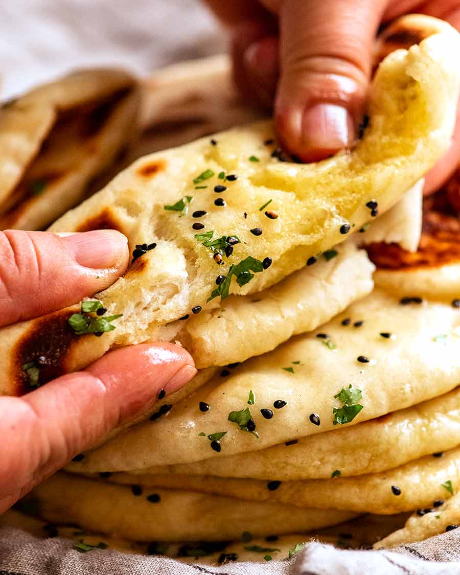 Tearing homemade naan to show how chewy it is