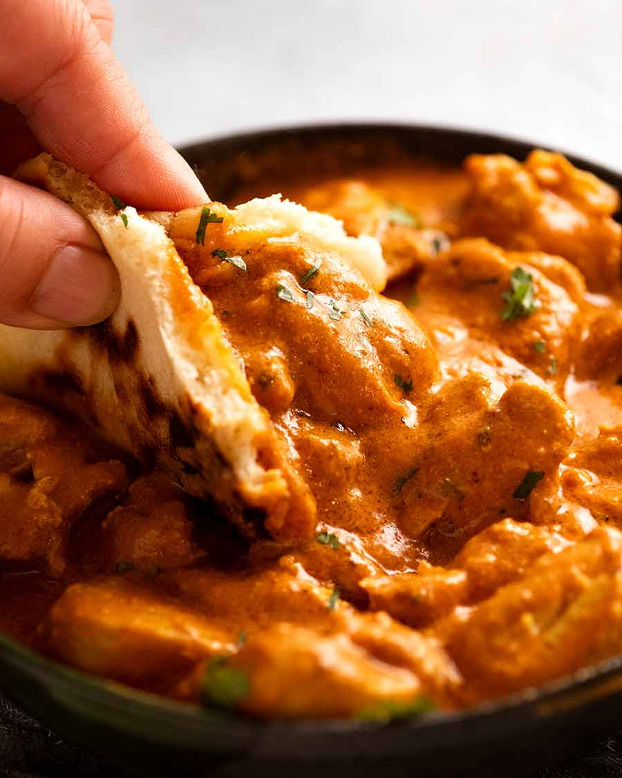 Scooping up Butter Chicken with fresh homemade naan