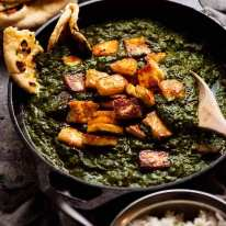 Freshly made Palak Paneer in a black skillet, fresh off the stove
