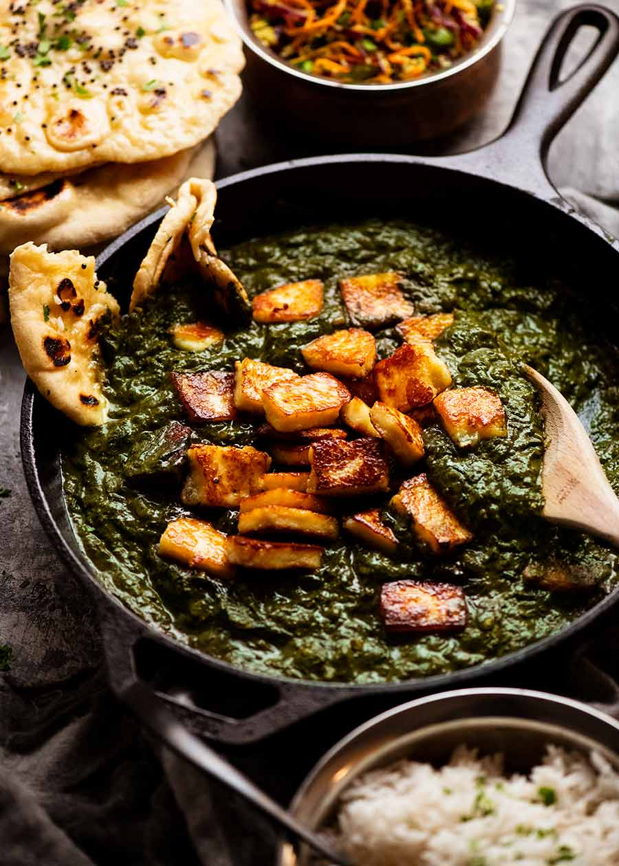 Palak Paneer - Indian Spinach Curry with Cheese in a black skillet, fresh off the stove