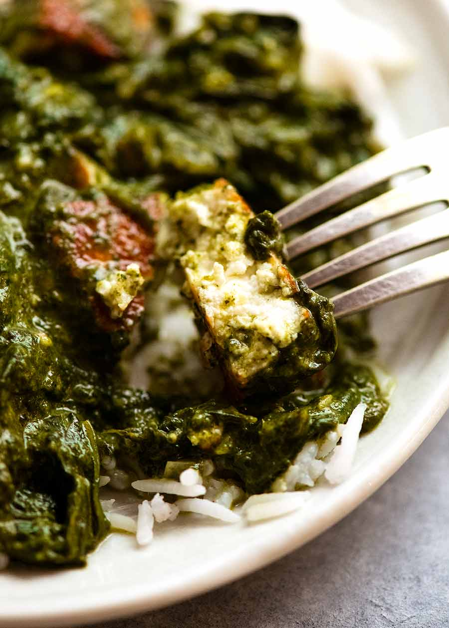 Close up of a piece of Paneer in Palak Paneer, showing creamy soft inside