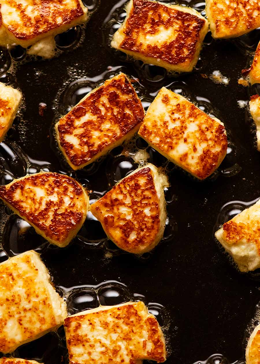 Paneer being pan fried in a skillet