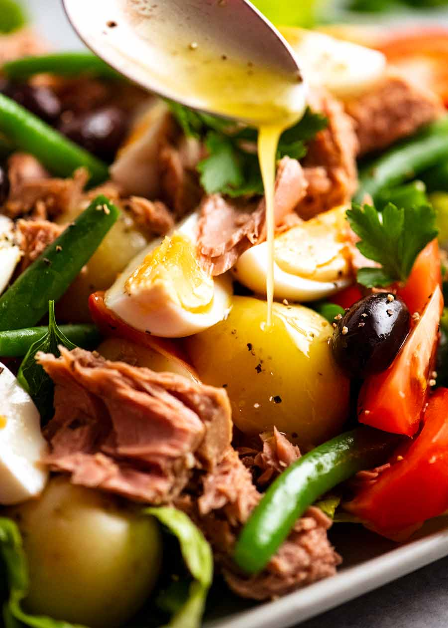 Drizzling lemon dressing over Salad Nicoise - French Tuna Salad