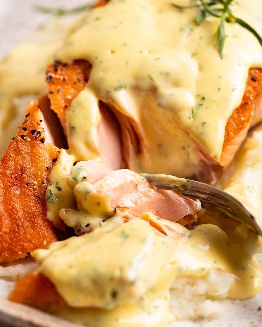 Close up of fork cutting into salmon with Bearnaise Sauce