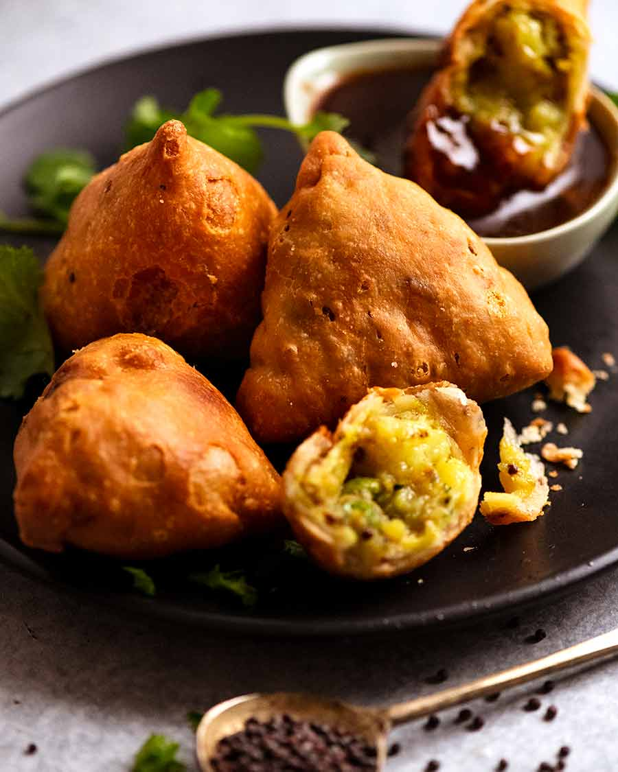 Samosas on a plate with tamarind dipping sauce