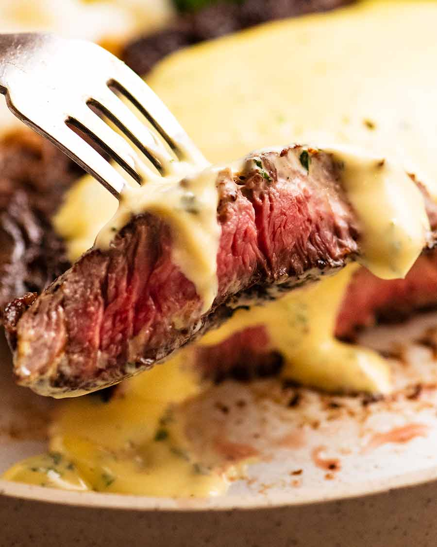 Close up of fork picking up a slice of steak with Bearnaise Sauce