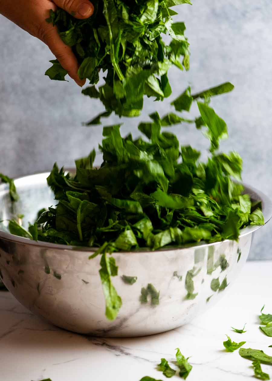Tumbling chopped fresh spinach into a big bowl