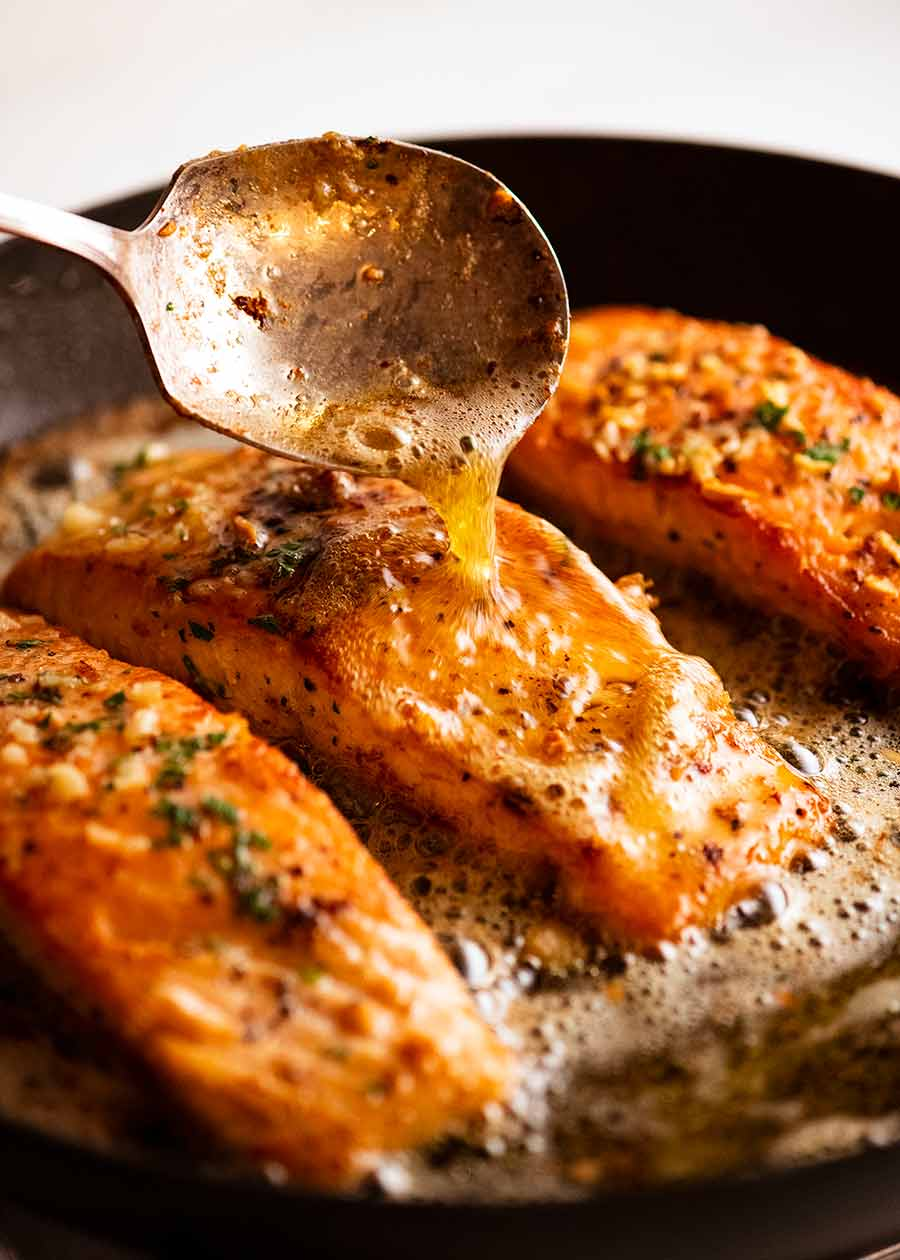 Spooning foaming melted butter over Garlic Butter Salmon