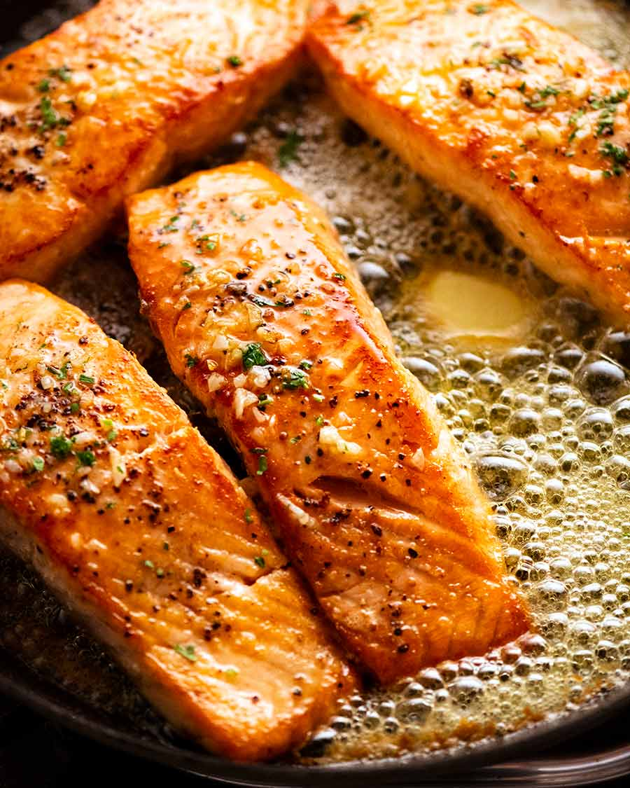Garlic Butter Salmon in a skillet surrounded by foaming garlic butter