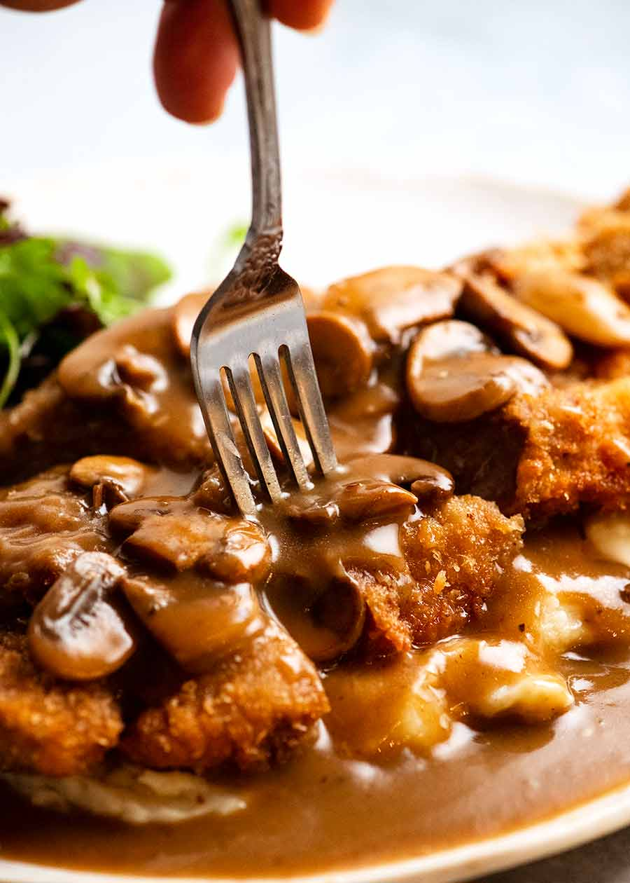 Fork picking up a piece of schnitzel smothered in Mushroom Gravy