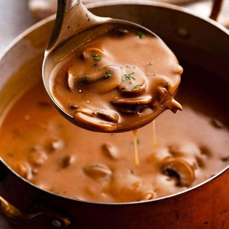 Ladle scooping up Mushroom Gravy from saucepan