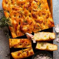 Overhead photo of Rosemary Garlic Focaccia on a wooden board, ready to be served