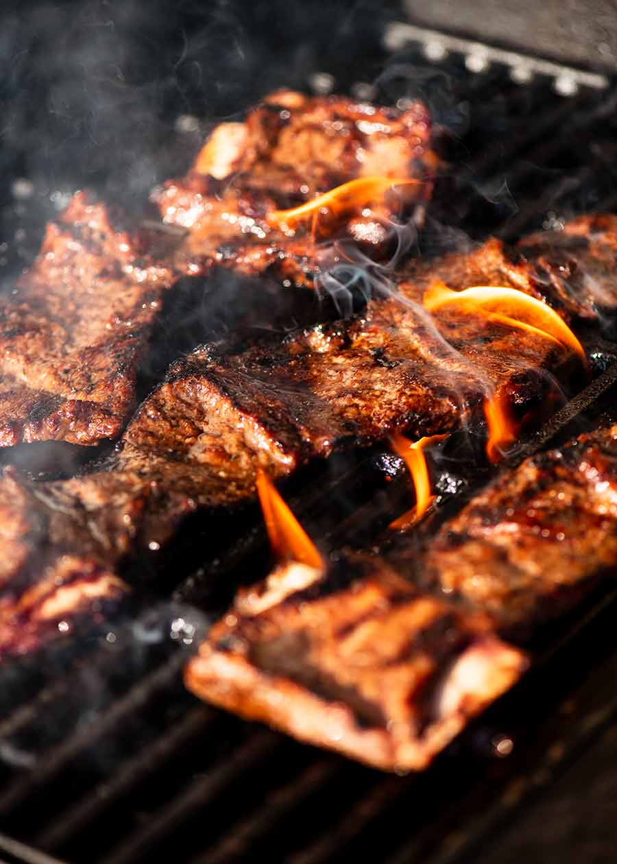 Korean BBQ Marinated Beef Short ribs (Galbi) cooking on a BBQ grill