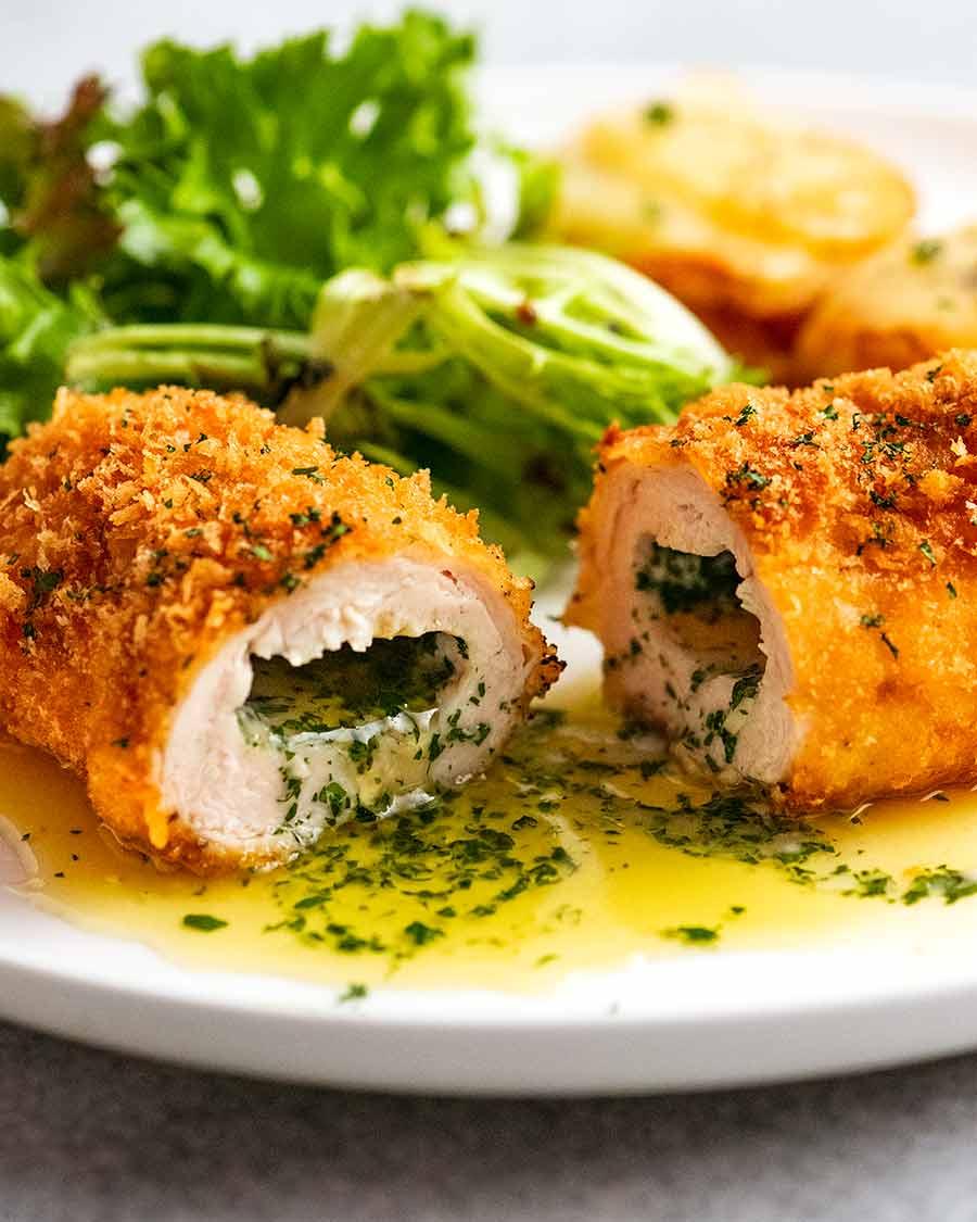 قطع قطعة مفتوحة من الدجاج كييف على طبق ، جاهزة للأكل