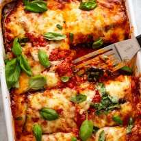 White baking dish with Eggplant Parmigiana, fresh out of the oven