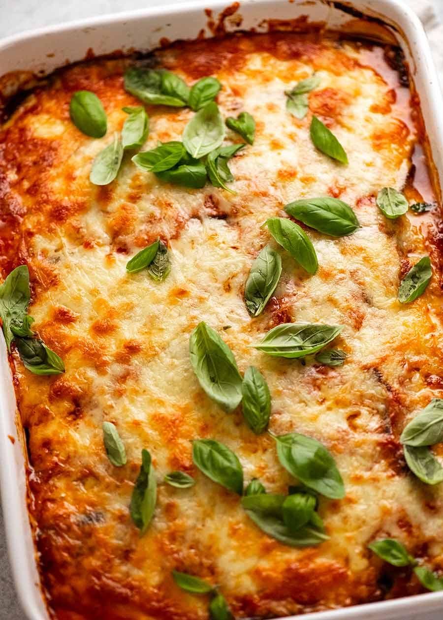 White casserole dish with freshly made Eggplant Parmigiana