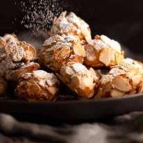 Dusting icing sugar over Italian Almond Cookies