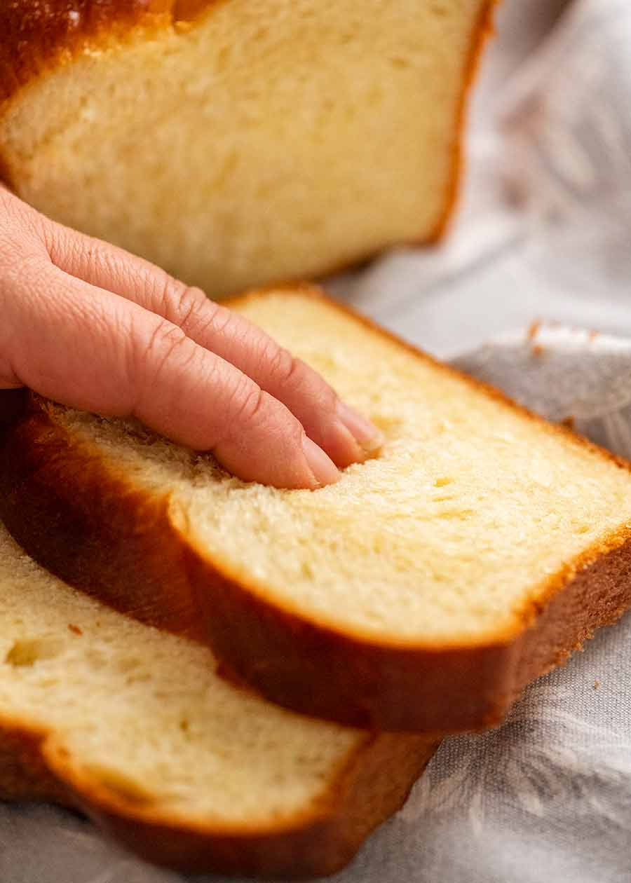 Hand touching brioche to show how soft it is