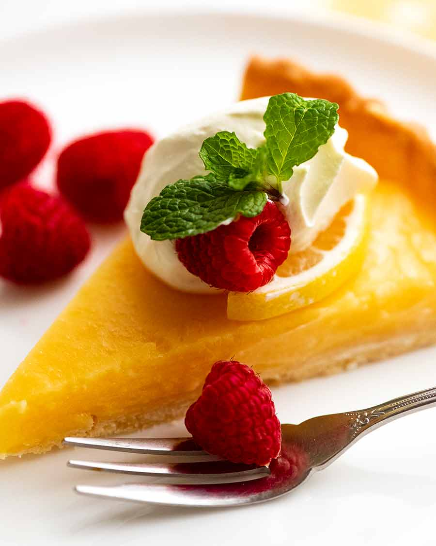 Close up photo of French Lemon Tart on a plate decorated with creme fraiche and raspberries