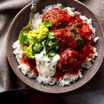 Overhead photo of Mexican Meatballs served with guacamole and sour cream over rice