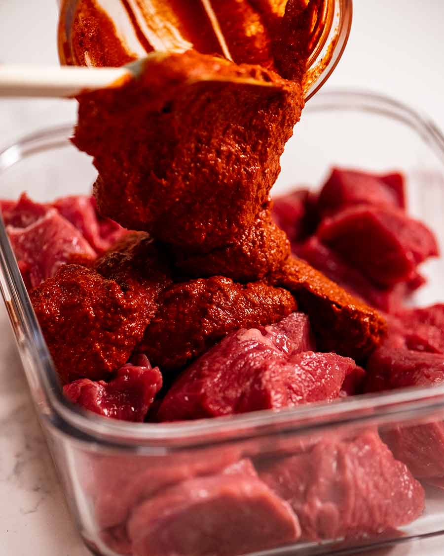 Pouring Vindaloo curry paste over beef to marinate