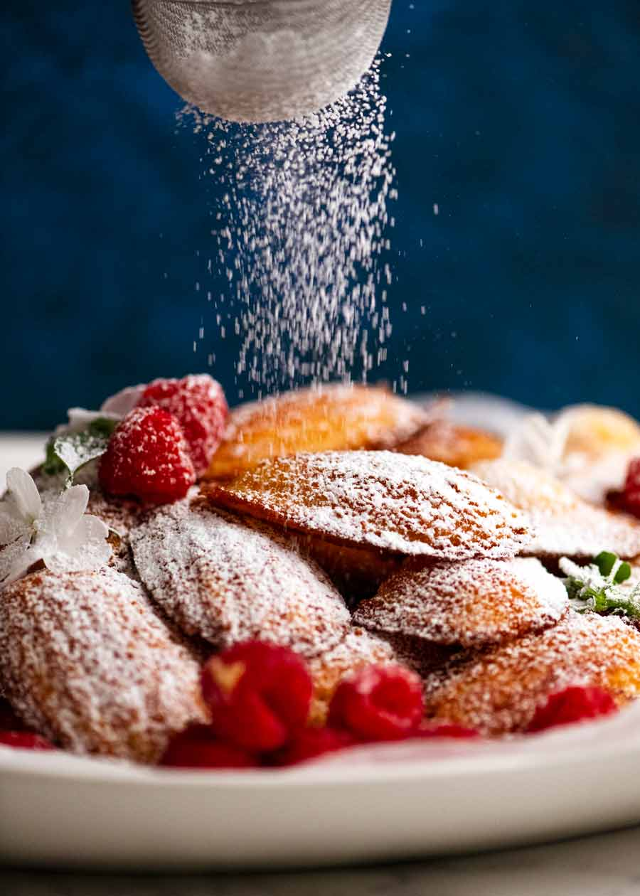 Dusting Madeleines with icing sugar