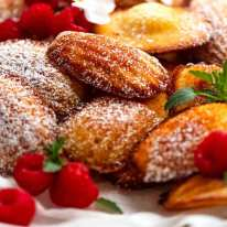 Close up of freshly made Madeleines dusted with icing sugar