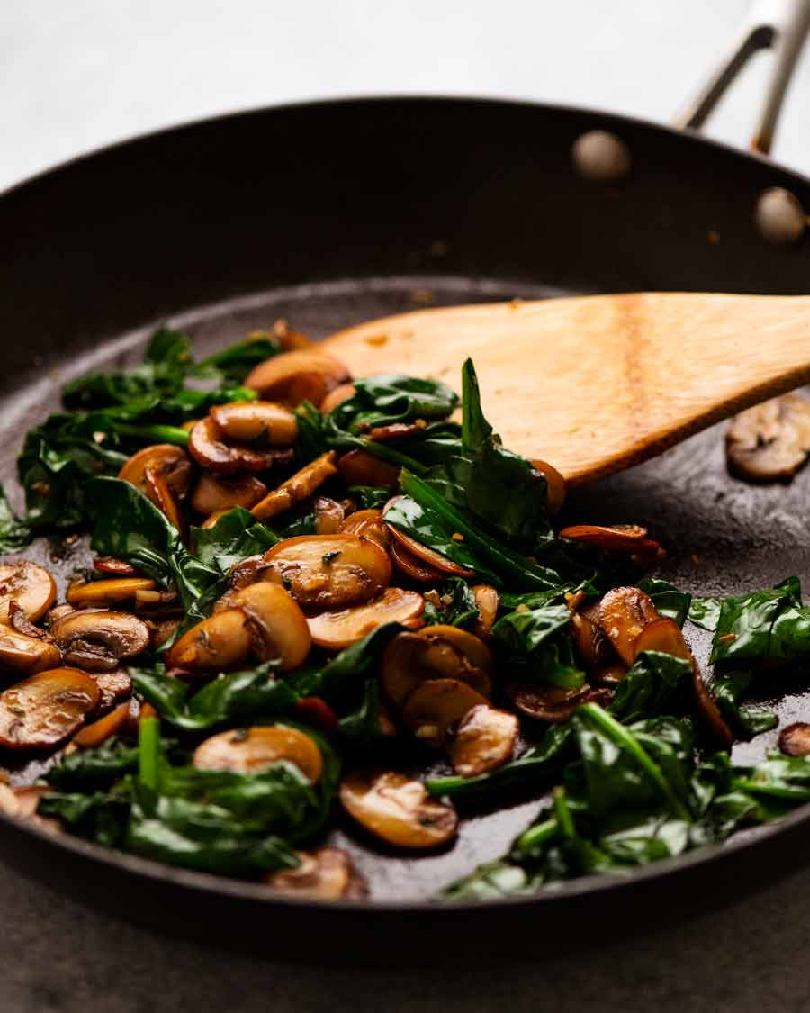 Skillet with sautéed mushrooms and spinach