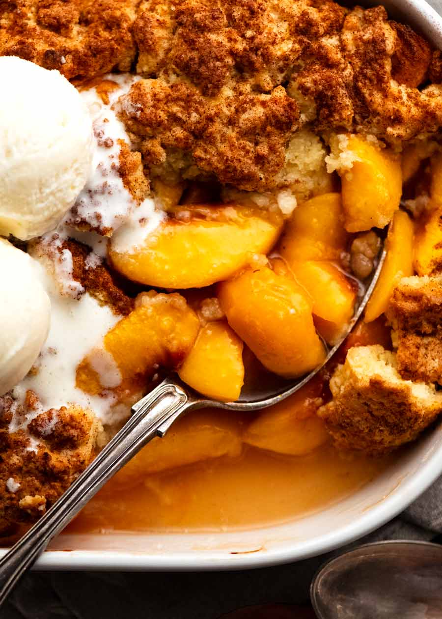 Close up scooping peaches out of Peach Cobbler in baking dish