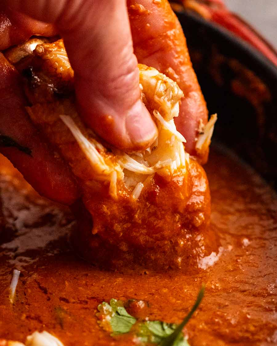 Dipping mud crab claw into Singapore Chilli Crab sauce