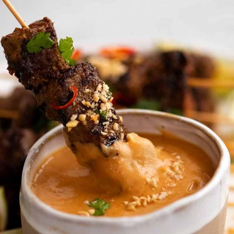 Dipping Thai Beef Satay into peanut sauce