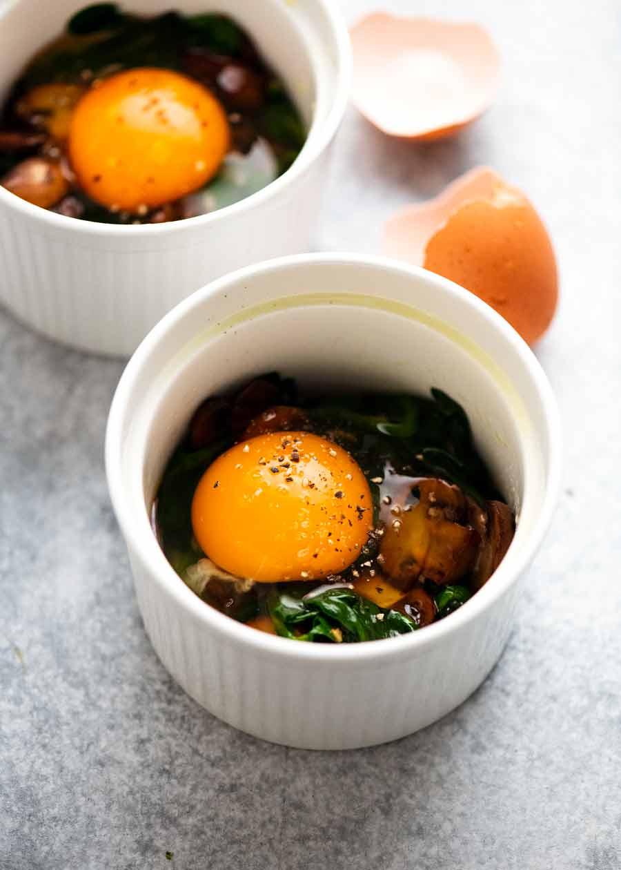 Raw eggs cracked into ramekins to make Baked Eggs - Shirred Eggs