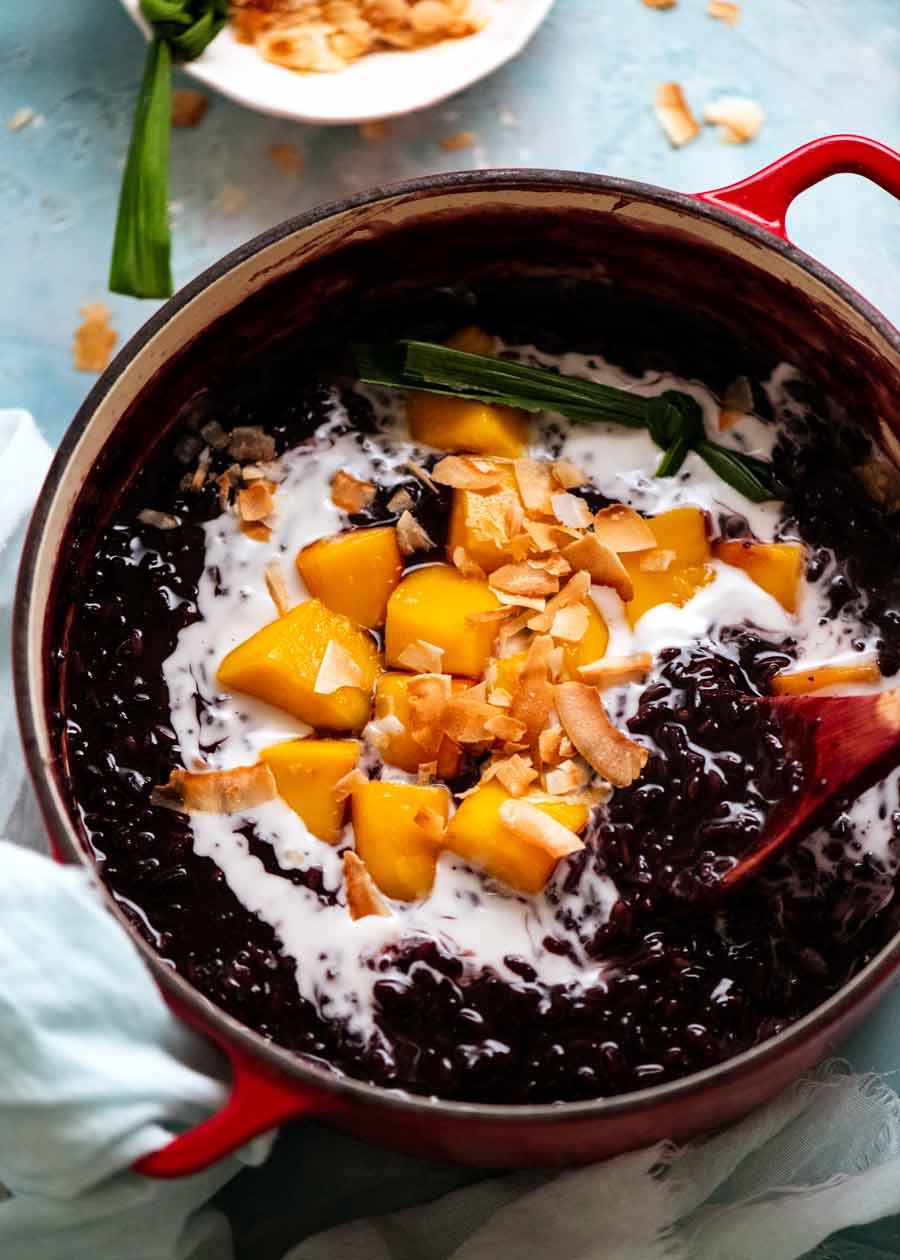 Thai Black Sticky Rice Pudding in pot with mango and coconut